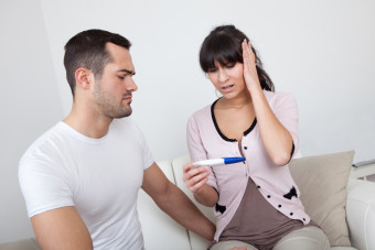 Young couple finding out results of pregnancy test at home