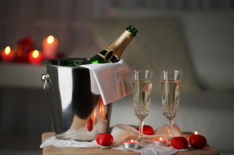 Champagne glasses and rose petals for celebrating Valentines Day, on dark background